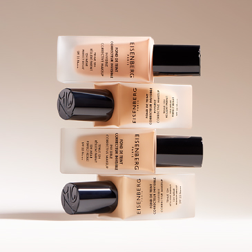 several corrective skin foundations stacked on a beige background