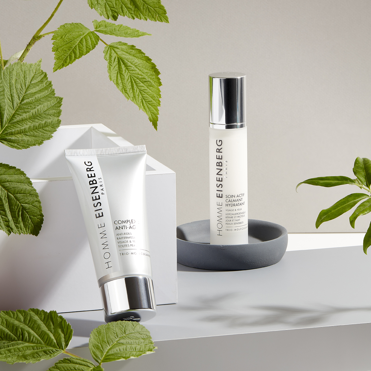 men's facial skincare with leaves on a grey and beige background