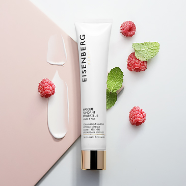 skincare for sensitive skin, the texture of whih is spread next to raspeberries and leaves, all placed against a pink and grey background