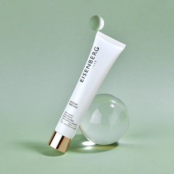 mattifying skincare leaned against a transparent bubble on a light green backgound