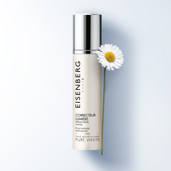 Dark spot serum and bellis prennis flower on a white-grey background